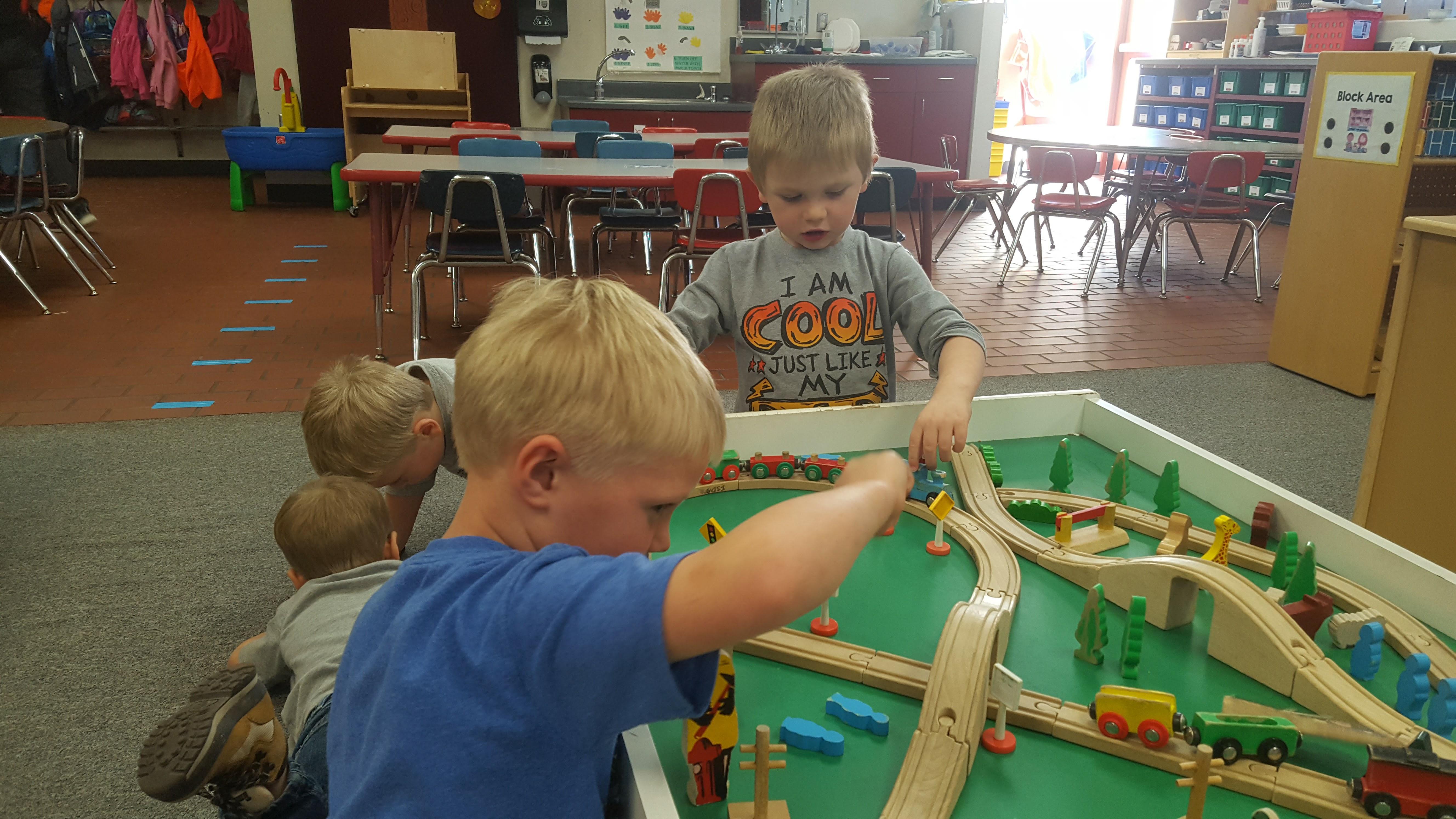 boys play on train table